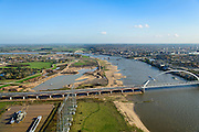Nederland, Gelderland, Nijmegen, 24-10-2013; <br /> De nieuwe stadsbrug van Nijmegen, De Oversteek.<br /> grondwerkzaamheden voor de dijkteruglegging Lent (Ruimte voor de Rivier). De dijken worden landinwaarts verplaatst en er wordt een nevengeul voor rivier de Waal gegraven. <br /> irst bridge the new city bridge of Nijmegen on the river Waal, De Oversteek (The Crossing). Next the railway bridge with cycle path De Snelbinder (The Luggage strap) and finally the Waal bridge. Right the groundworks for the Dike relocation of Lent (project Ruimte voor de Rivier: Room for the River). <br /> luchtfoto (toeslag op standaard tarieven);<br /> aerial photo (additional fee required);<br /> copyright foto/photo Siebe Swart.