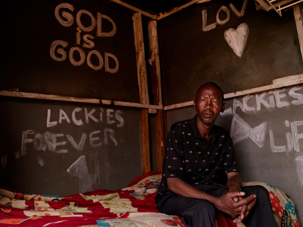 """Remembrance Nhlahla Tlhabanelo, born in 1969, joined the MK in the early 80s.  He currently lives in a shack made of tine and cardboard in the front yard of a friend's bar.  When asked what he was trained to do with the MK he directly responds:  """"My specialty was to kill. Guerrilla warfare""""."""
