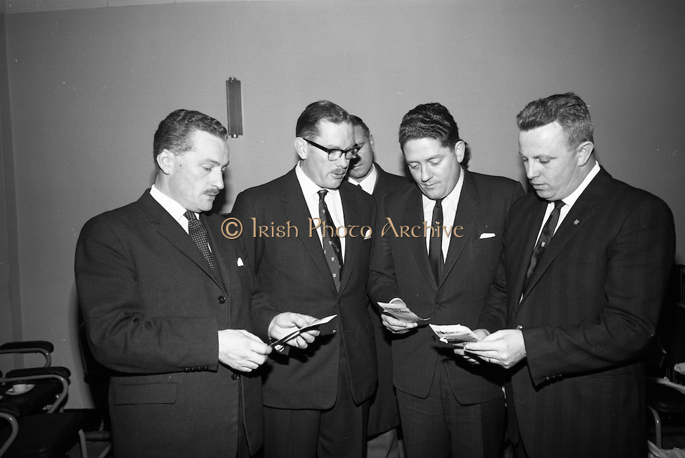 """Presentations at Shell and BP, Fleet Street..1964..18.12.1964..12.18.1964..18th December 1964..At Shell & BP house in Fleet Street, Dublin, the Minister for Justice, Mr Brian Lenihan TD was on hand to present prizes to young winners in """"The Pink Paraffin""""competition...Image shows The Minister for Justice, Mr Brian Lenihan TD, and officials from Shell & BP checking the names of the prize winners at the start of the event."""
