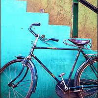 A Vintage Bicycle Waits by Stairs with Silver Chai Tea Cup In Delhi, India