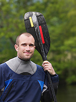 Man with kayak paddle outdoors portrait