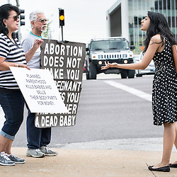 "Lisa Johnston  |  lisajohnston@archstl.org  |  @aeternusphoto  After recent videos from an antiabortion group were released apparently showing a Planned Parenthood official discussing the method and price of providing fetal tissue left over from abortions for medical research, protesters gathered outside of the Planned Parenthood facility on Forest Park Blvd. in St. Louis. Mary Maschmeier, executive director, Defenders of the Unborn, talked to passersby on the sidewalk in front of Planned Parenthood. Fajer Saeed of St. Louis took exception with the demonstrators arguing that Planned Parenthood does not sell aborted fetuses, calling the circulating video a ""(fxxxing) hoax."" Also pictured is demonstrator Rudy Mendez."