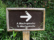 A sign directing visitors to Machu Picchu in Spanish (top) and English (bottom).