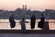 Local men on the West Bank of the river Nile talk at dawn on railings overlooking the city of Luxor, Nile Valley, Egypt.