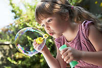 Girl Blowing Soap Bubbles in backyard close up