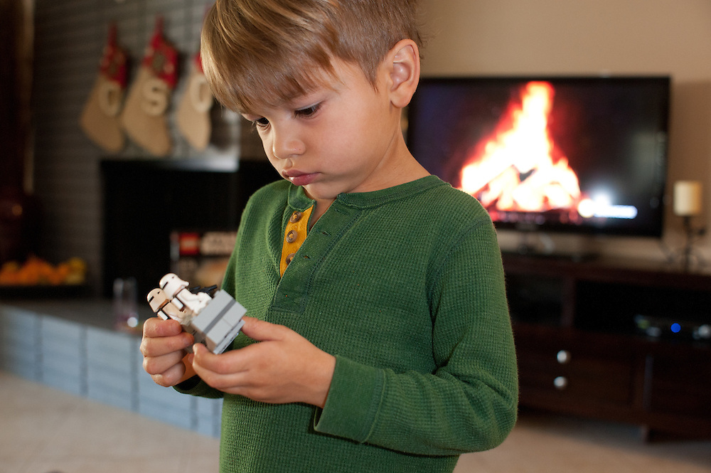 young boy looking at Star War's toy, Christmas-stockings and TV with fireplace image in the background