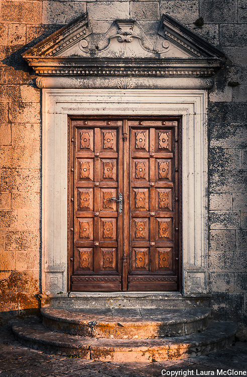 Brown Carved Door with Stone Surround in evening light, Croatia