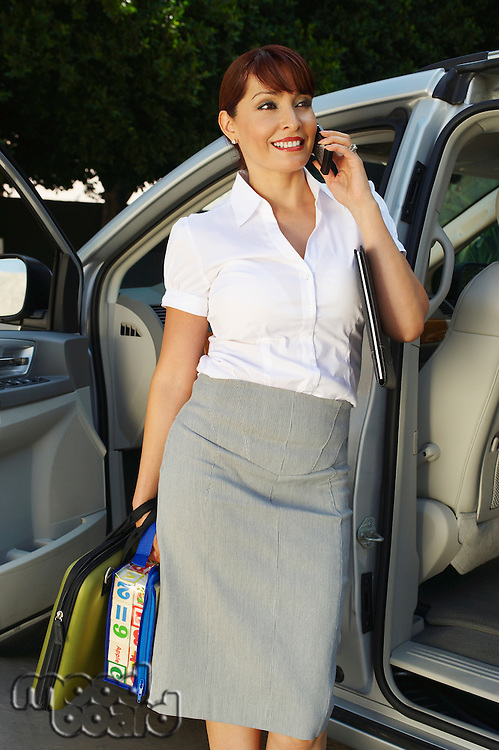 Business woman using mobile phone beside car