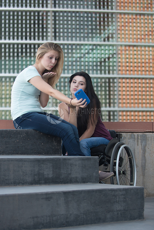 Two girls using cell phone to take photo (selfie). One girl uses a wheelchair.