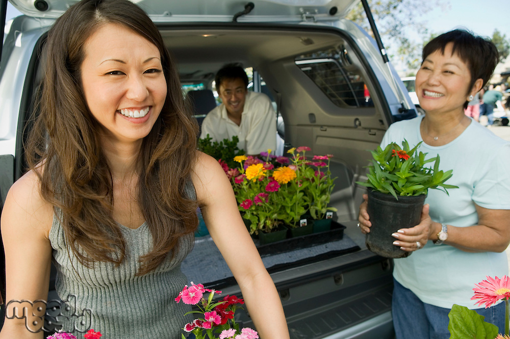 Family loading flowers into back of SUV portrait