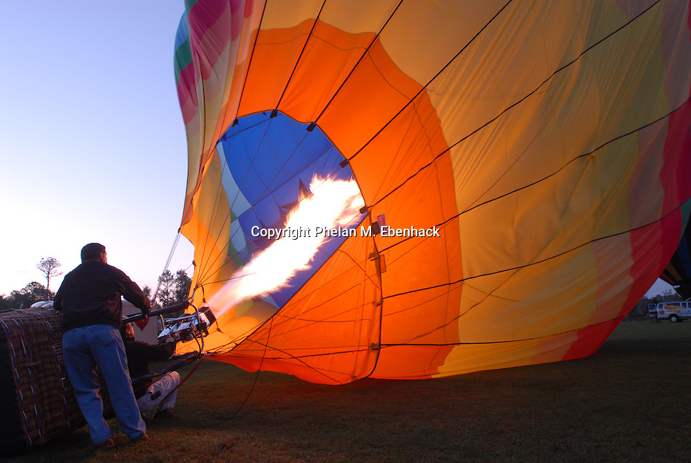An operator fills a hot air balloon before taking flight from a field as the sun rises in Kissimmee, Florida.