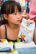 "23 APRIL 2013 - BANGKOK, THAILAND:   A Thai girl waits to donate a book to a Thai literacy project during the opening ceremony to mark Bangkok as the World Book Capital City 2013. UNESCO awarded Bangkok the title. Bangkok is the 13th city to assume the title of ""World Book Capital"", taking over from Yerevan, Armenia. Bangkok Governor Suhumbhand Paribatra announced plans that the Bangkok Metropolitan Administration (BMA) intends to encourage reading among Thais. The BMA runs 37 public libraries in the city and has modernised 14 of them. It plans to build 10 more public libraries every year. Port Harcourt, Nigeria will be the next World Book Capital in 2014..PHOTO BY JACK KURTZ"