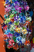 Garlands of foil pompom Christmas decorations hang in a Oaxaca shop, Mexico.