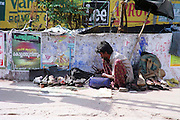 a men selling used shoes on the street, India, Kerala, a state on the tropical coast of south west India