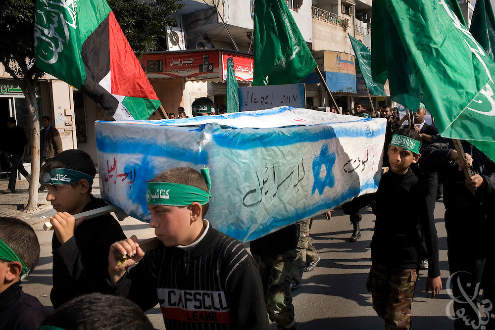 """Palestinian boys carry a mock Israeli coffin during a """"Victory"""" parade thrown by militant Palestinian political group HAMAS January 20, 2009 in Gaza City. Several thousand marchers celebrated what HAMAS called the defeat of Israel during the recent 21 day offensive by Israeli forces against HAMAS fighters. During the operation more than 1500 Palestinians were killed and more than 4000 homes destroyed in the narrow Gaza Strip."""
