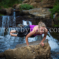 woman in small steam on rock near waterfall doing yoga hand balance
