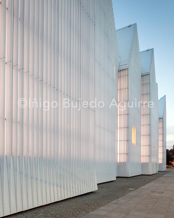 Dusk perspective of luminous exterior facade. Szczecin Philharmonic Hall, Szczecin, Poland. Architect: Estudio Barozzi Veiga, 2014.