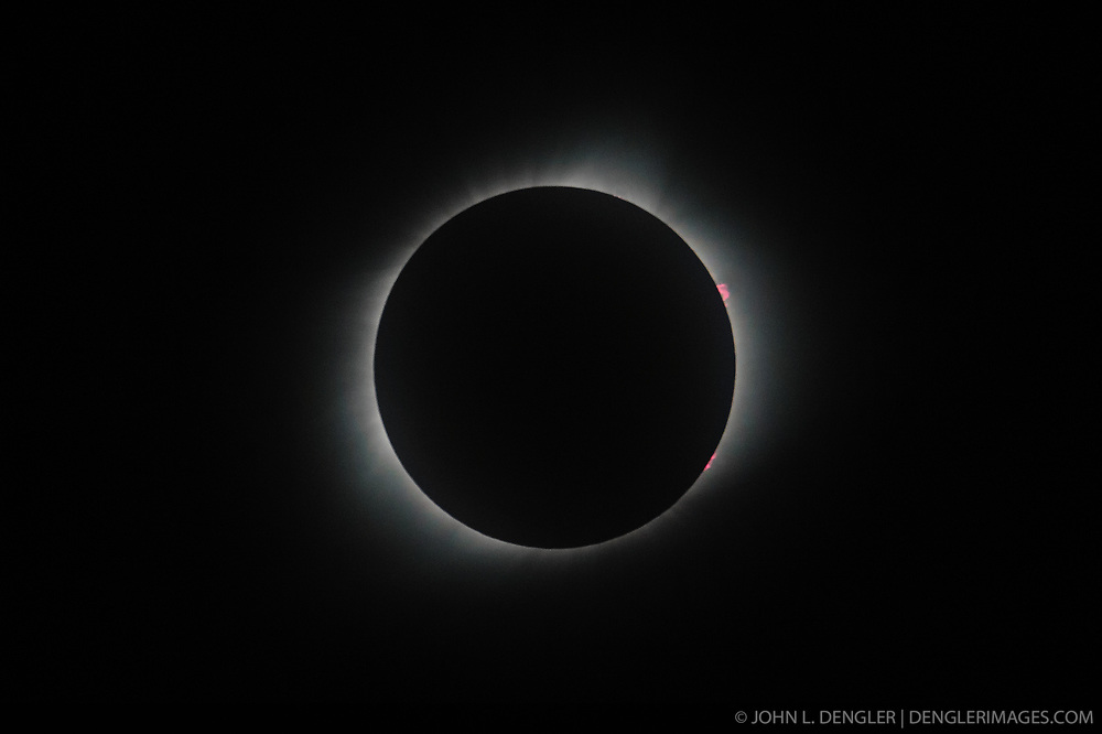 Solar prominences (electric pink in color) are visible in this photo taken during a total eclipse of the sun. Solar prominences are formed from hot hydrogen gas rising from the lower regions of the sun&rsquo;s atmosphere known as the chromosphere. Rising from tens of thousands of miles above the sun&rsquo;s surface, they can be seen past the moon during a total solar eclipse.<br /> <br /> Also visible is the white corona that surrounds the sun. This photo was taken in Columbia Mo. at the Columbia Audubon Nature Sanctuary in Columbia, Mo. on August 21.<br /> <br /> A solar eclipse occurs when a full moon passes between the sun and Earth and blocks the sun when they are in alignment with each other as seen from Earth. The astronomical term for this alignment is known as syzygy.<br /> <br /> The August 21, 2017 eclipse was viewed by millions as it raced across the continental United States from Oregon to South Carolina. The last total eclipse in the continental United States was in 1979. The last total eclipse in Missouri was in 1869. While total solar eclipses will hit any one spot on Earth every 375 years, they take place somewhere about once every 18 months.<br /> <br /> The next total eclipse to have its path through Missouri will occur in 2024.