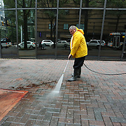 Charlotte, NC- September 22, 2016: Scott, an employee of the Omni Hotel, uses a pressure washer to remove blood and dirt from the sidewalk in front of the hotel. CREDIT: LOGAN R CYRUS FOR THE NEW YORK TIMES