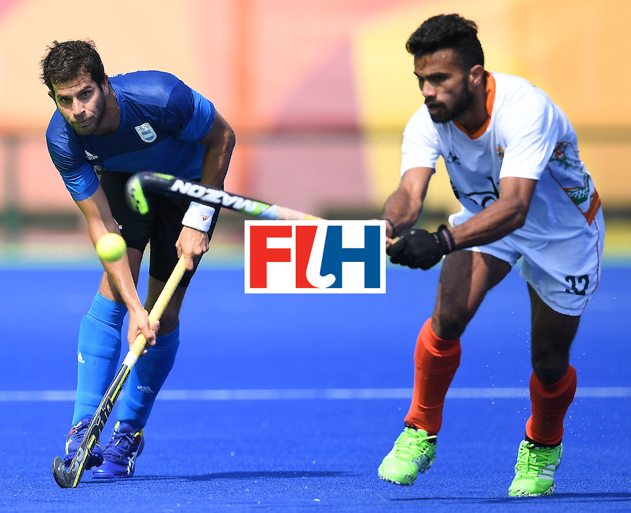 India's Chandanda Thimmaiah vies for the ball with Argentina's Juan Lopez during the men's field hockey Argentina vs India match of the Rio 2016 Olympics Games at the Olympic Hockey Centre in Rio de Janeiro on August, 9 2016. / AFP / MANAN VATSYAYANA        (Photo credit should read MANAN VATSYAYANA/AFP/Getty Images)
