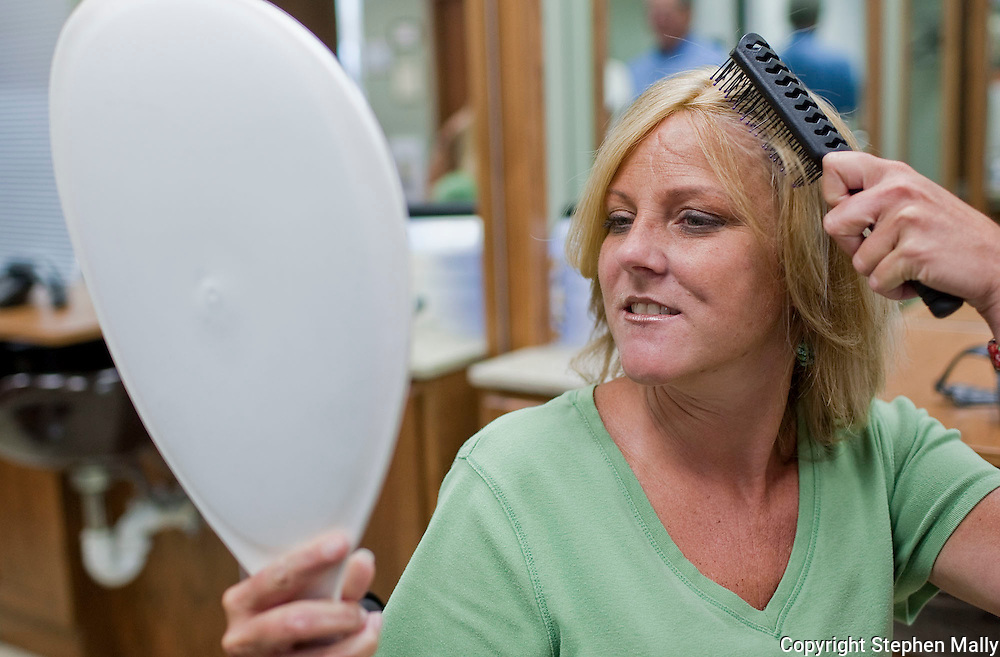 Gina Judkins brushes her new hair at Advanced Hair Technologies in Hiawatha on Saturday, May 29, 2010. Judkins was given 6 months to live after being diagnosed with brain cancer. After 6 surgeries, chemotherapy and radiation she has been cancer free for 14 years.