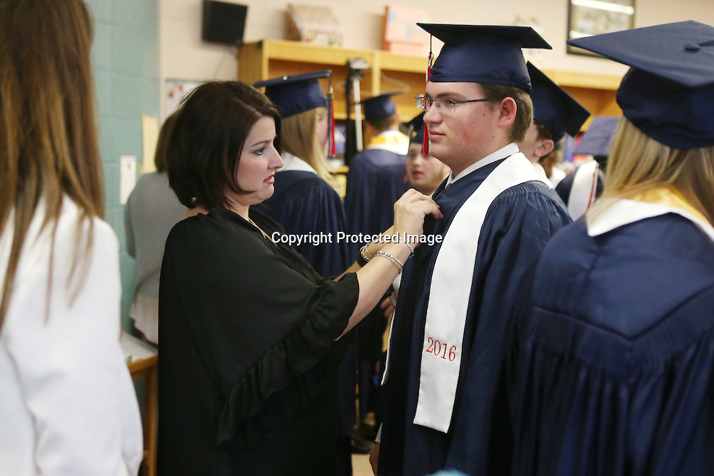 Lauren Wood | Buy at photos.djournal.com<br /> Teacher Blair Waver pins John Boatner's stole in the library Friday evening before the Baldwyn High School commencement ceremony at the high school.