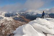 Hill walker on the summit of Tom na Gruagaich (922m) in winter, Beinn Alligin, Torridon, Scotland