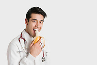 Portrait of Indian male doctor eating banana over white background