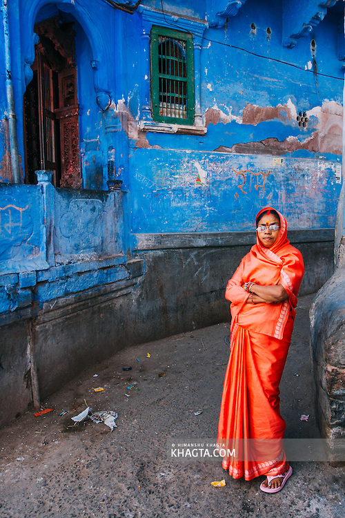 Portrait of a Rajasthani lady wearing bright orange Saree in the blue streets of Jodhpur