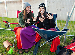 © Licensed to London News Pictures. 24/06/2015. Pilton, UK.   Festival goers arrive at Glastonbury Festival 2015 Wednesday Day 1 of the festival. It is just after dawn and people have been travelling thoughout the night.       These girls have just finished painting their nails bright colours.  The pedestrian gates to the festival opened at 8am this morning, with many festival goers arriving and waiting throughout last night for the opening.  This years headline acts include Kanye West, The Who and Florence and the Machine, the latter having been upgraded in the bill to replace original headline act Foo Fighters.  Photo credit: Richard Isaac/LNP