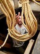 Deckhand Dan Roche reaches to receive a coil of cordage from 2nd Mate Sean Bercaw as the crew loads the whaleship Charles W. Morgan Friday, May 16, 2014 at the Mystic Seaport's H.B. duPont Preservation Shipyard. The Morgan, the last remaining wooden whaling ship remaining and the oldest American commercial vessel still in existence as well as a National Historic Landmark, will embark on the first leg of its 38th voyage, a tour of historic New England ports, this weekend.  (Sean D. Elliot/The Day)