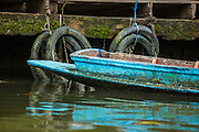 "17 NOVEMBER 2012 - BANGKOK, THAILAND:  A blue canoe tied up a dock on a canal in the Thonburi section of Bangkok. Bangkok used to be known as the ""Venice of the East"" because of the number of waterways the criss crossed the city. Now most of the waterways have been filled in but boats and ships still play an important role in daily life in Bangkok. Thousands of people commute to work daily on the Chao Phraya Express Boats and fast boats that ply Khlong Saen Saeb or use boats to get around on the canals on the Thonburi side of the river. Boats are used to haul commodities through the city to deep water ports for export.    PHOTO BY JACK KURTZ"