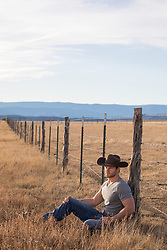cowboy taking a break by a rustic fence on a ranch