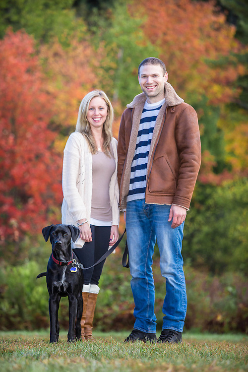 Young couple with black lab mix at park in Carlisle, MA.