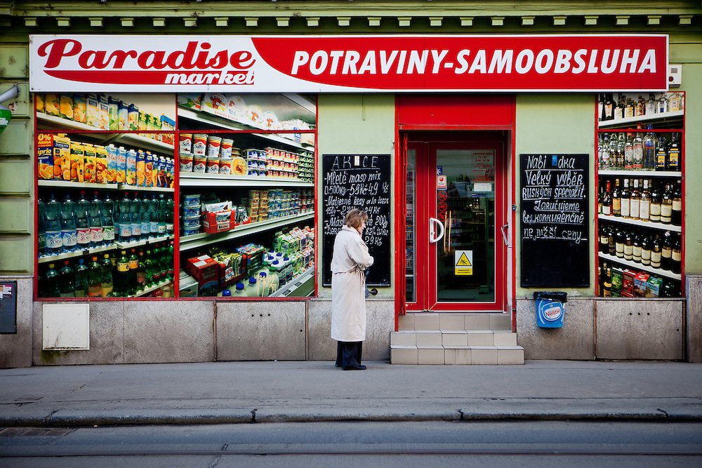 "Woman infront of a ""Paradise market"" in Prague Zizkov."