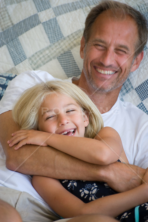 Father and daughter laughing together on a plaid quilt