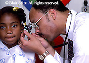 Doctor, Physician at Work African American Physician and Black Female Child Patient