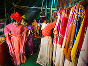 "30 JUNE 2016 - BANGKOK, THAILAND: Performers change into the costumes before a Chinese opera performance at Chiao Eng Piao Shrine in Bangkok. Chinese opera was once very popular in Thailand, where it is called ""Ngiew."" It is usually performed in the Teochew language. Millions of Chinese emigrated to Thailand (then Siam) in the 18th and 19th centuries and brought their culture with them. Recently the popularity of ngiew has faded as people turn to performances of opera on DVD or movies. There are about 30 Chinese opera troupes left in Bangkok and its environs. They are especially busy during Chinese New Year and Chinese holidays when they travel from Chinese temple to Chinese temple performing on stages they put up in streets near the temple, sometimes sleeping on hammocks they sling under their stage.       PHOTO BY JACK KURTZ"