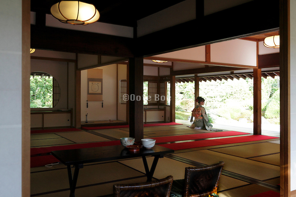 young woman in kimono sitting and looking out into the garden inside a traditional Japanese house