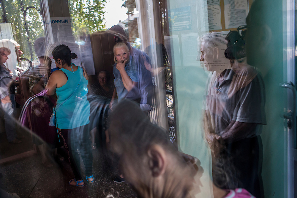 SARTANA, UKRAINE - AUGUST 29, 2015: People await the start of humanitarian aid distribution in Sartana, Ukraine. The village of Sartana, on the northeastern outskirts of Mariupol, has been relatively close to the front line between Ukrainian and pro-Russian rebel forces, with many incidents of shelling damaging homes and injuring or killing civilians. CREDIT: Brendan Hoffman for The New York Times