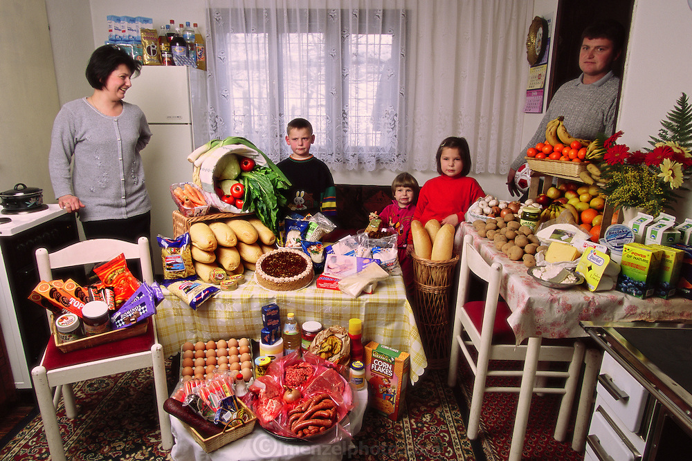 (MODEL RELEASED IMAGE). The Dudo family in the kitchen/dining room of their home in Sarajevo, Bosnia and Herzegovina, with one week's worth of food. Standing between Ensada Dudo, 32, and Rasim Dudo, 36, are their children (left to right): Ibrahim, 8, Emina, 3, and Amila, 6. Cooking methods: electric stove, coal/wood stove. Food preservation: refrigerator-freezer. /// The Dudo family is one of the thirty families featured in the book Hungry Planet: What the World Eats (p. 46). Food expenditure for one week: $167.43 USD. (Please refer to Hungry Planet book p. 47 for the family's detailed food list.)