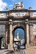 Tourists in horse-drawn carriage pass Triumphal Arch and Spitalskirche in Innsbruck, the Tyrol, Austria
