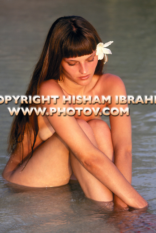 Naked young woman sitting in shallow water, wearing flower in hair. (Skinny-Dipping).
