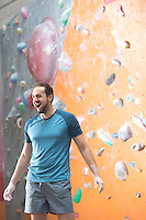 Dedicated man shouting by climbing wall in crossfit gym