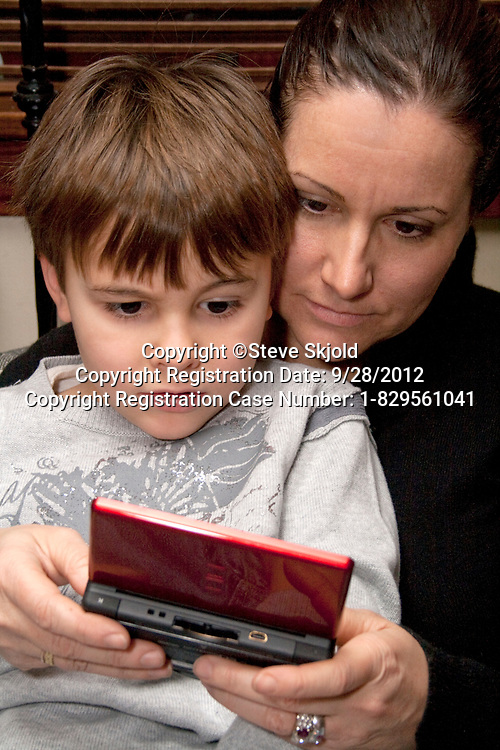 Mom and son age 40 and 5 playing a video game on his hand-held mobile electronic device. St Paul Minnesota MN USA