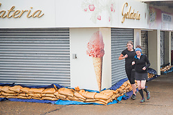 © Licensed to London News Pictures. 21/10/2017. Brighton, UK. Shops on the Brighton seafront have protected their premises with sandbags as powerful gusts of wind and rain are hitting Brighton and Hove as storm Brian hits the South Coast. Photo credit: Hugo Michiels/LNP