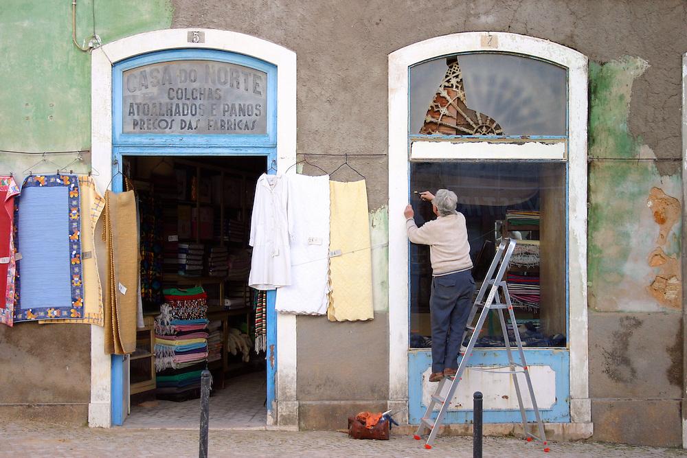 Shopkeeper repairs a window, fabric store, Tavira Portugal