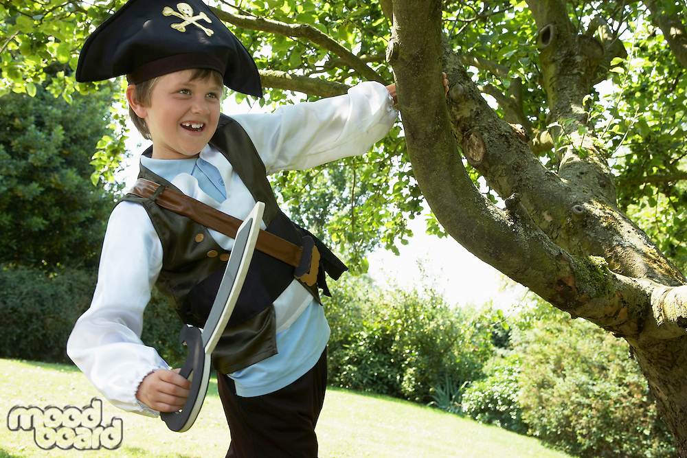 Boy Wearing Pirate Costume swinging from tree in park