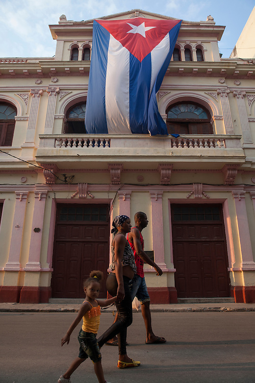 A family walks down San Miguel street, by a large Cuban flag, in Centro Habana, in Havana, Cuba.