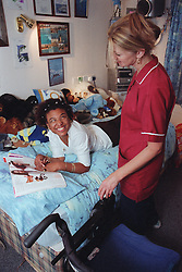Care manager in residential care centre discussing magazine article with young woman with Cerebral Palsy,